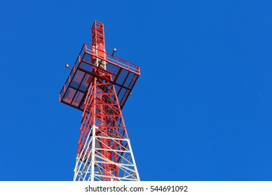 Red metal column holding some wireless radio and cellular antennas
