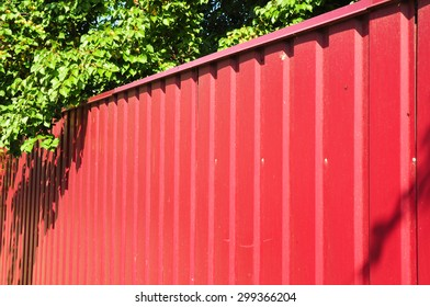 Red metal fence on the street side.