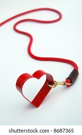 Red metal heart on the end of a red leash, isolated on white