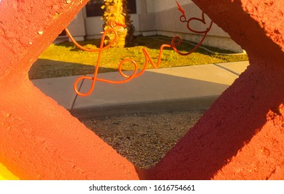 A red metal script sign saying LOVE with a heart at the end lies between a maroon and yellow painted block with a palm tree in the background