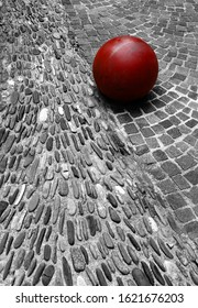 Red metal sphere on stone pavement