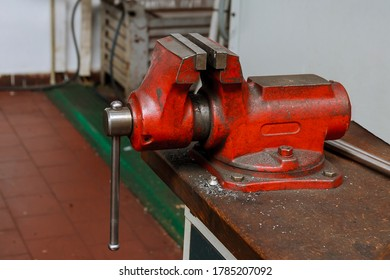 Red Metal vice on wooden table on factory