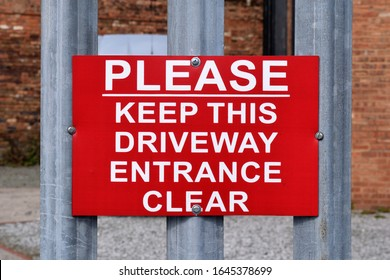 Red Metal Warning Sign on Steel Fence 'Please Keep This Driveway Entrance Clear'