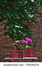 Red metallic chair, a vase with flowers on a table against a stoned wall covered with green ivy.