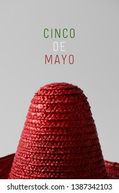 a red Mexican hat and the text Cinco de Mayo, May 5 in Spanish, a popular Mexican holiday that commemorates de victory at the Battle of Puebla, written in the colors of the Mexican flag