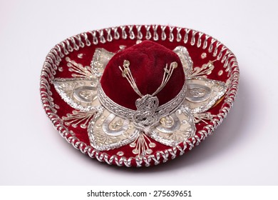 Red mexican sombrero with silver galloon on white background