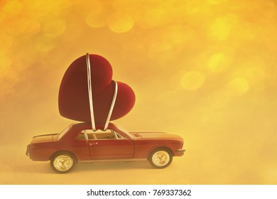 Red miniature car with a heart on the roof. Yellow background with bokeh