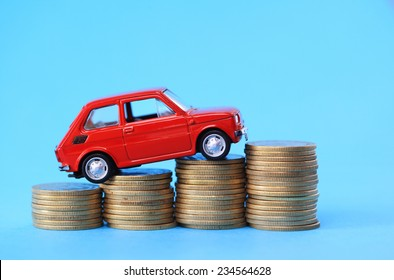 Red miniature car on coin stack