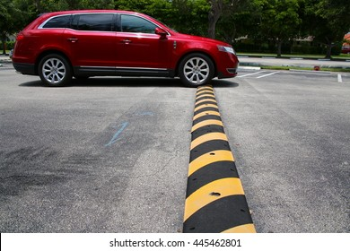 Red Minivan Driving Up to and Just Connecting with Yellow and Black Striped Speed Bump in Parking Lot with Diagonal Striped Spaces and Trees in the Background, Mid-Day