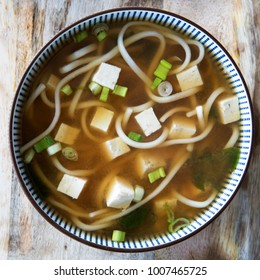 Red miso soup with tofu, green onions and udon noodles.  Square orientation, close-up flat lay.