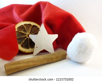 Red mitre, cinnamon stick, an orange slice and a wooden star