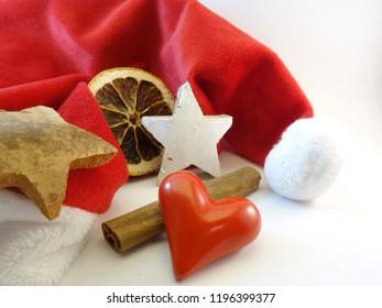 Red mitre, cinnamon stick, wooden star, heart and orange slice