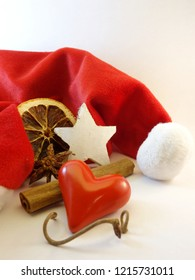 Red mitre, cinnamon stick, wooden star, heart, twig, anise and orange slice