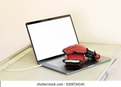 red mixed martial arts gloves on the computer laptop on the white desk. laptop display white screen.