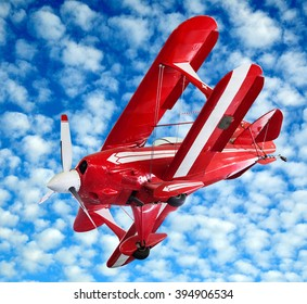 Red model vintage biplane flying midair and banking against a cloudy blue sky