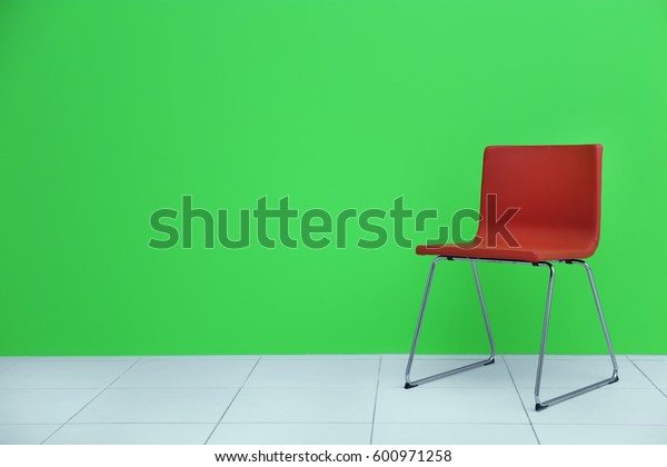 Red modern chair on green wall background