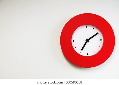 Red modern wall clock on white concrete wall