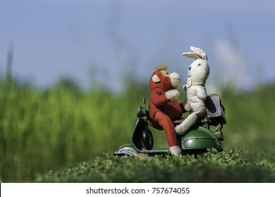 Red monkey doll with white rabbit doll on motorcycle toy  in the field