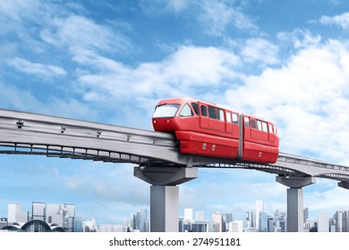 Red monorail train against blue sky and modern city in background