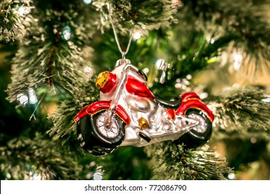 Red motorcycle ornament is hanging on the Christmas tree.