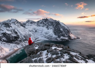Red mountaineer sightseeing on ridge with arctic ocean in Ryten mountain at evening