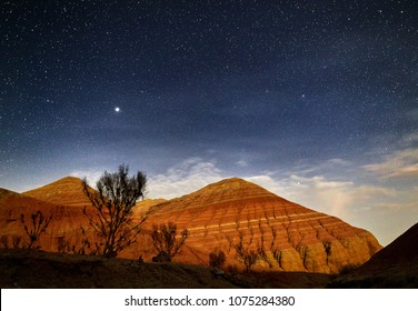 Red mountains in the canyon desert at night starry sky background. Astronomy photography of space and landscape.