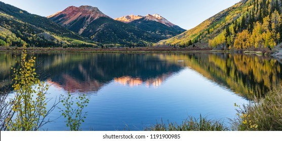The Red Mountains and golden aspens on Hayden Mountain reflected in Crystal Lake in the Uncompahgre National Forest south of Ouray, Colorado.  (panorama)