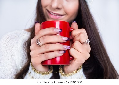 A red mug with coffee in hands of a girl with manicure, long hair and white sweater no face