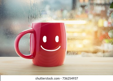 Red mug of coffee with a happy smile, Steaming red coffee cup on a rainy day window background, Good morning or have a happy day message concept