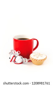Red mug filled with black coffee ,decorated with white jingle bells, silver metallic ribbon, and a mince pie on white background.