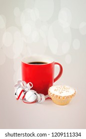 Red mug filled with black coffee ,decorated with white jingle bells, silver metallic ribbon, and a mince pie on gray bokeh background.