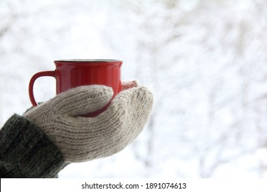 a red mug in the hands of those dressed in knitted mittens against the backdrop of a blurred snow landscape. a warming drink for a winter morning