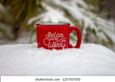 Red mug hot beverage steam rising relax more worry less message on front surrounded by snowy scene and icy pine branches in winter background, holiday stress keep calm relax more worry less concept