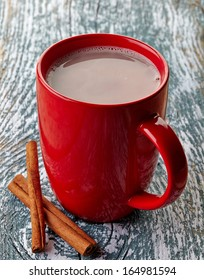 Red mug of hot chocolate drink with cinnamon sticks