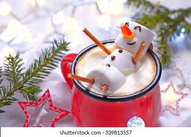 Red mug with hot chocolate with melted marshmallow snowman - Shutterstock ID 339813557