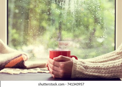 red mug of hot drink in hand, when behind is window is rain / cozy home atmosphere in autumn