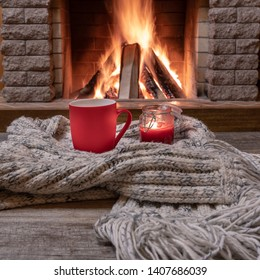 Red mug with hot tea, and a candle , wool scarf, near cozy fireplace, in country house, hygge, home sweet home.