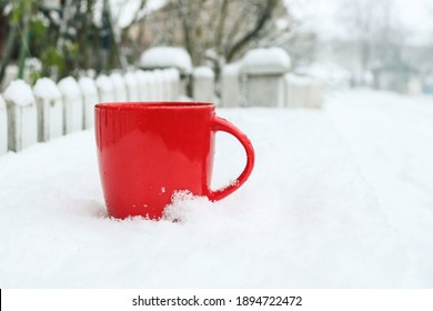 Red mug on a winter snowy background. Outdoors. Winter concept.