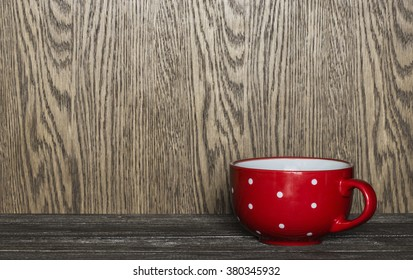 Red mug with polka dots in the corner of the table on a wooden background