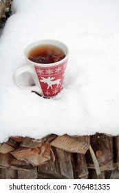 red mug with spiced tea in the snow