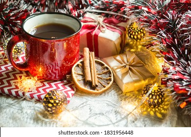 Red mug with tea in Christmas decorations on a white knitted blanket. New year, garlands, gifts, cinnamon and dried orange - an atmosphere of warmth, comfort and magic.