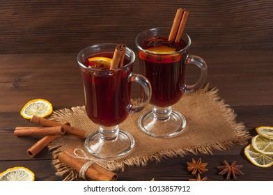 Red mulled wine on burlap on a wooden table with various spices