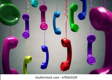 Red and multi-coloured telephone receiver hanging over gray background concept for on the phone, customer service, on hold or contact us