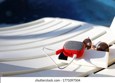 Red music portable speaker is charged from the power bank via usb on a deck chair near the pool. Concept is always in touch, travel gadgets, external battery for a smartphone. Place for text. Flatlay
