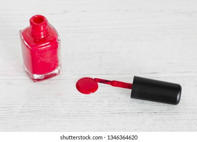 red nail polish bottle on wooden surface spilling color, concept of beauty industry
