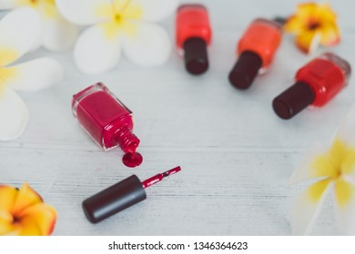 red nail polish bottle and other colors on wooden surface with flowers around it, concept of cosmetics industry and manicure