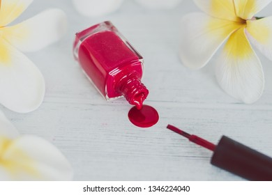 red nail polish bottle spilling color on wooden surface with flowers around it, concept of cosmetics industry and manicure