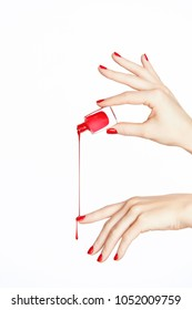 Red Nail Polish. Hand With Red Nails On White Background. Close Up Of Female Hands With Smooth Soft Skin And Bright Color Manicure Pouring Nail Polish From Bottle. High Quality Image.