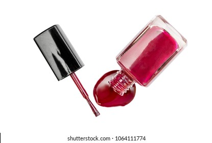 Red nail polish spilled from the bottle with brush on white background. Top view.