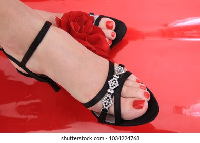 red nails on the feet on the red background